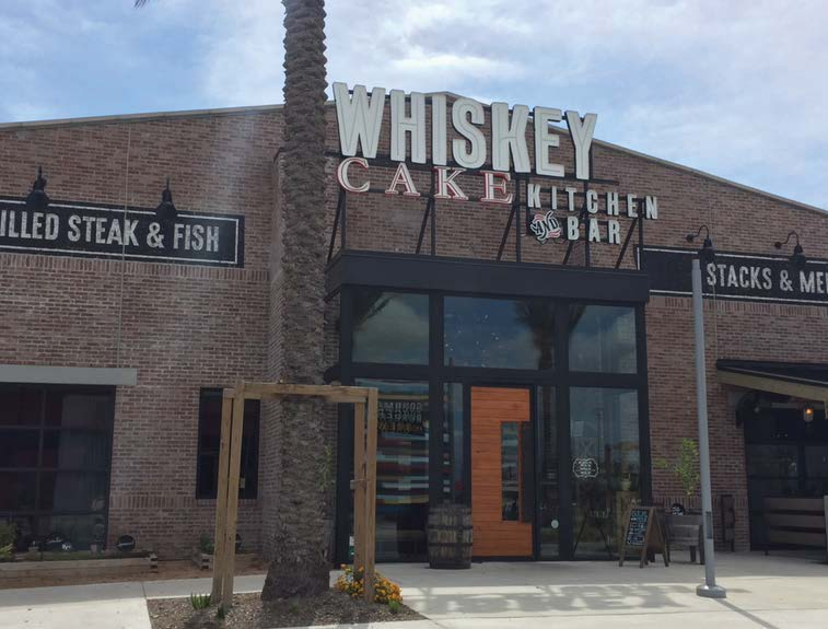 picture of entrance to whiskey cake showing doors and a brick store front